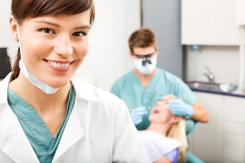 female dentist with patient in background